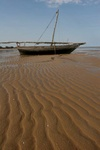 fishing boat and sand waves at low tide in the Indian Ocean
